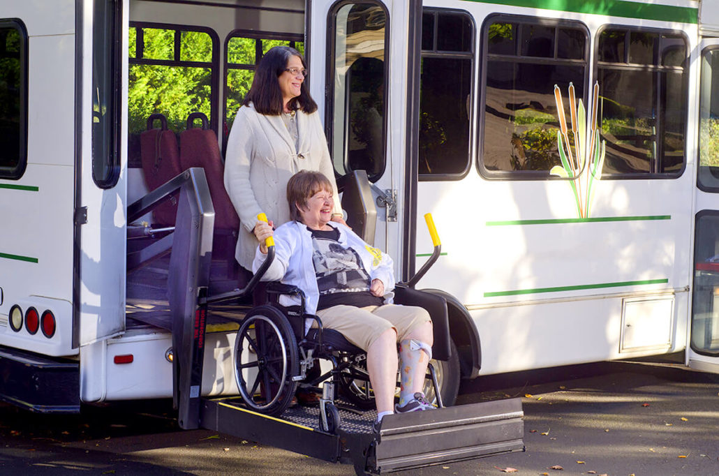 woman helping another woman off a bus using a wheelchair lift at the Towncenter assisted living community