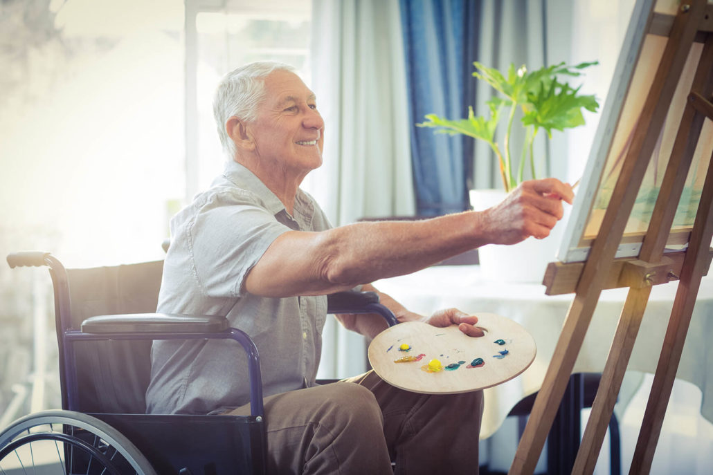 man in a wheel chair painting at the Towncenter assisted living community