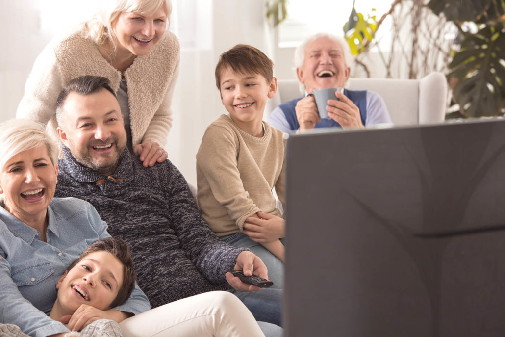family laughing and watching TV