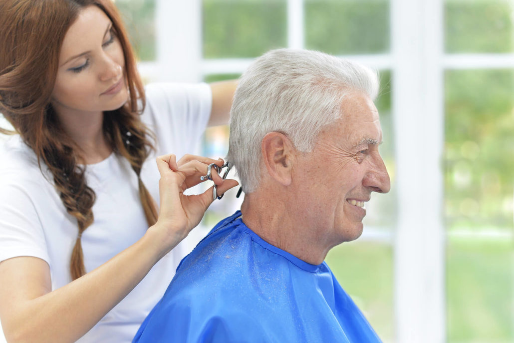 older gentleman getting a hair cut at the Towncenter assisted living community salon