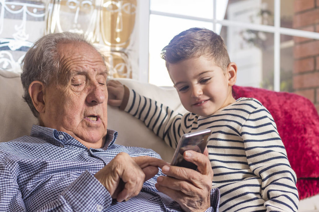elderly man and child using a cell phone